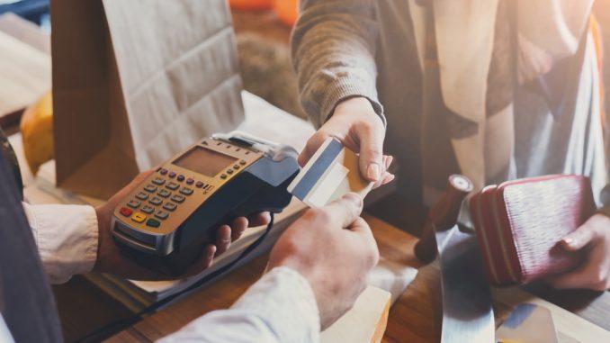 persona pagando con tarjeta asociada a club premier